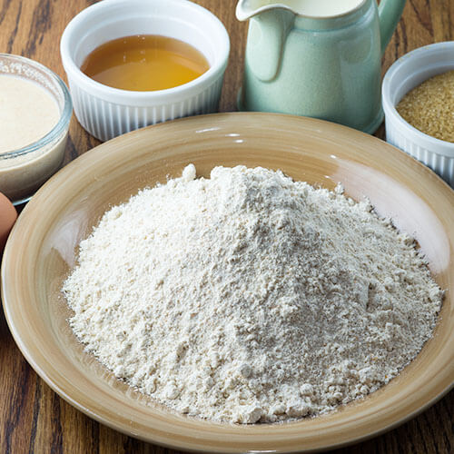 array of ingredients for making bread, including a plate of flour