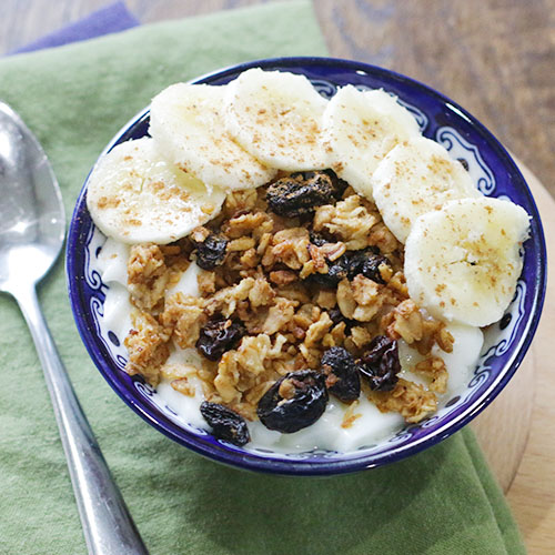 pretty blue bowl filled with homemade granola and yogurt, garnished with banana slices and cinnamon