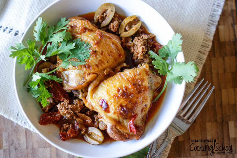 citrus herb basque chicken in a dish with sprigs of parsley