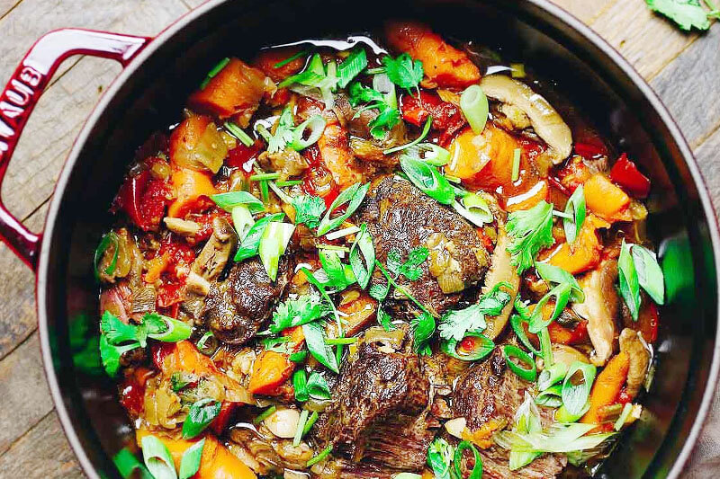 enameled cast iron skillet full of beautiful taiwanese beef stew with fresh herbs on top