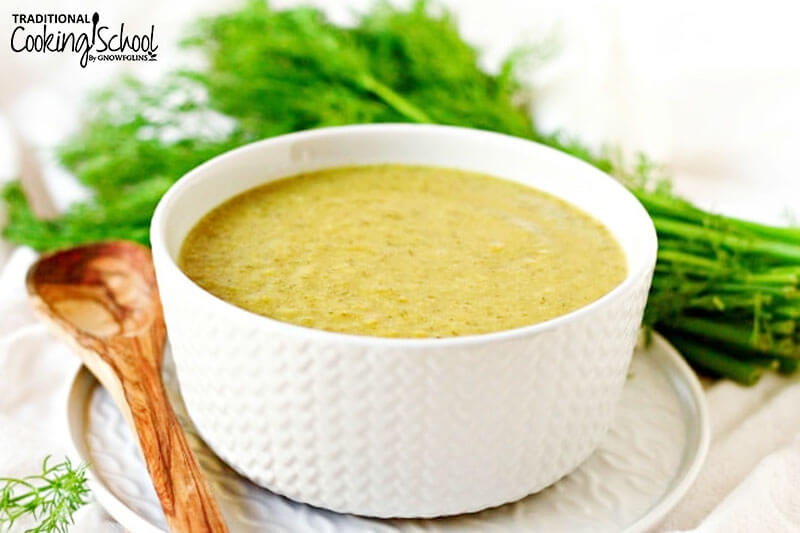 bowl of creamy broccoli dill soup next to a wooden spoon