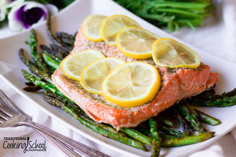 salmon filet on a bed of asparagus with lemon slices on top
