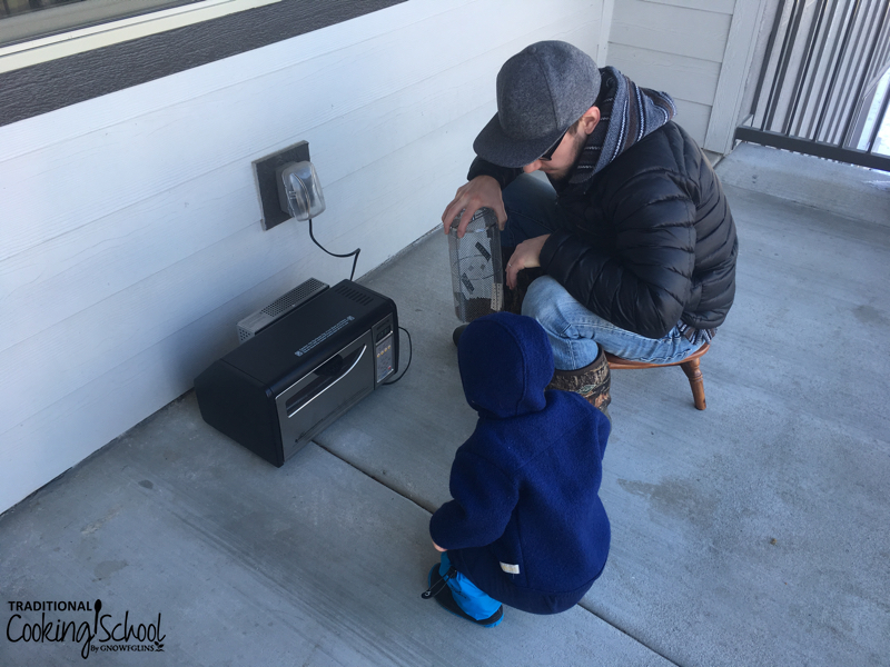 man and boy roasting coffee on an outside patio in the winter