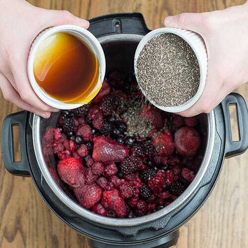 overhead shot of making Instant Pot jam, with hands holding two little white ceramic bowls of ingredients, pouring them into the insert pot which is already full of frozen berries
