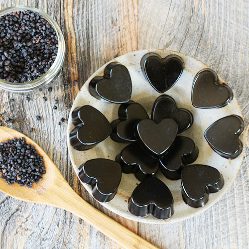 a small jar and spoonful of elderberries on a wooden table next to a plate of heart-shaped elderberry gummies