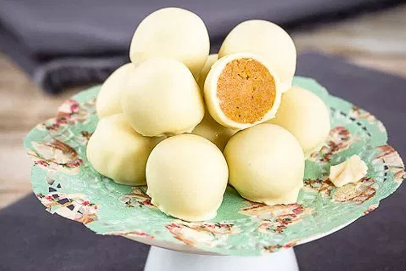 pumpkin white chocolate desserts stacked on serving tray on gray napkin