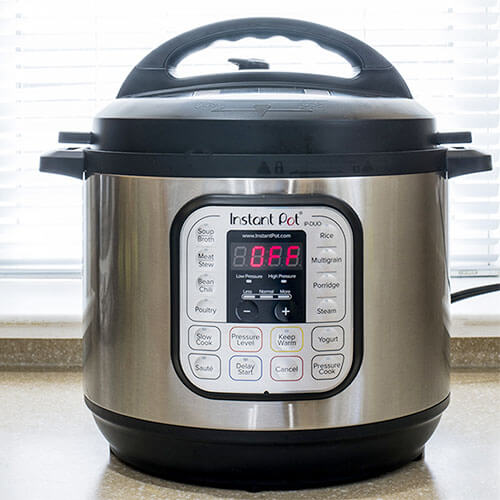large 8 quart Instant Pot DUO sitting on a countertop behind a window with the blinds drawn