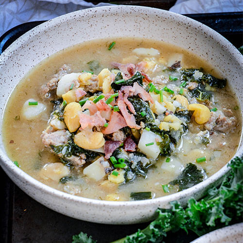 healthy fava bean soup packed with veggies and garnished with bacon and chives