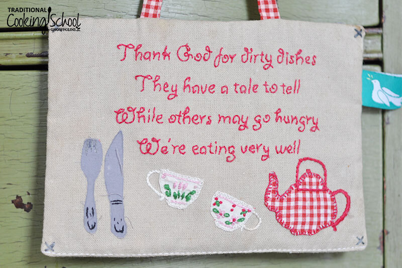 "photo of handmade sign embroidered in pink thread with these words: ""Thank God for dirty dishes / They have a tale to tell / While others may go hungry / We're eating very well"""