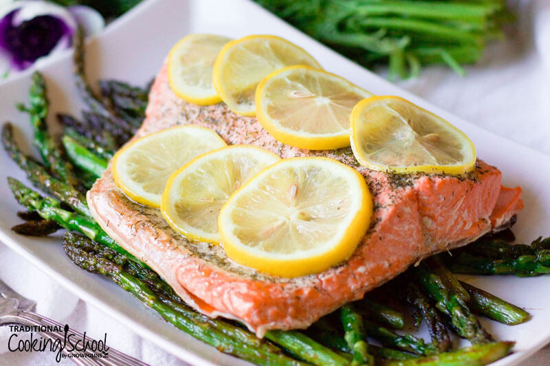 salmon filet on bed of roasted asparagus with lemon slices on top