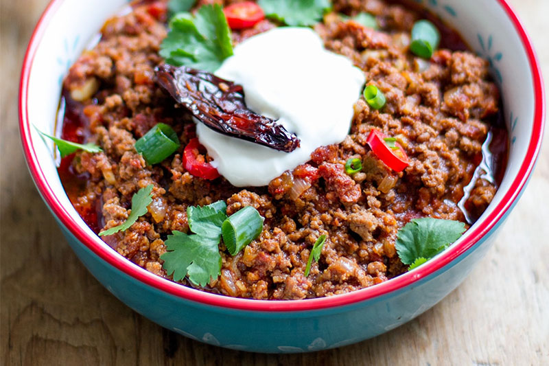 big bowl of healthy chili, garnished with chives, parsley, sour cream, and a sundried tomato