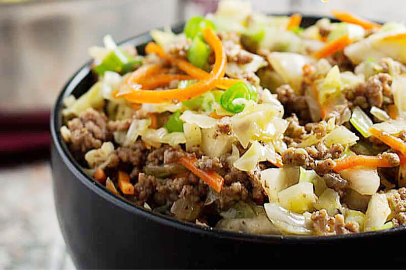 egg roll in a bowl topped with generous amounts of cabbage, carrots, and chives