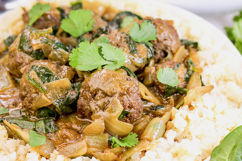 Creamy Coconut Meatball Korma over a bed of rice garnished with cilantro