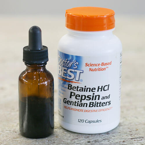 tincture in a small glass dropper bottle next to a white plastic bottle of Betain HCl Pepsin and Gentian Bitters on a counter