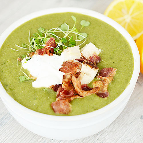 big bowl of beautiful fresh green blended soup garnished with microgreens, sour cream, chicken, and bacon