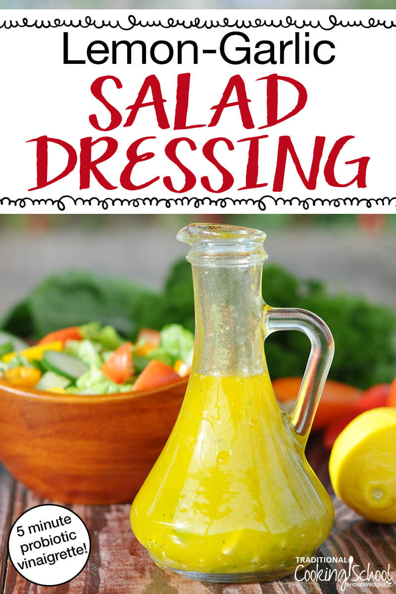 """beautiful glass container full of healthy salad dressing with a wooden bowl of salad in the background and text overlay: """"Lemon-Garlic Salad Dressing (5 minute probiotic vinaigrette!)"""""""