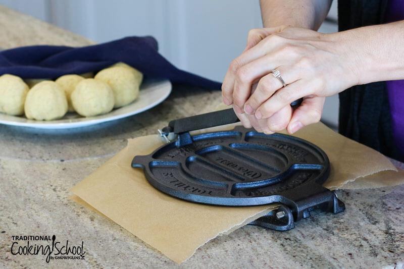 woman using a cast iron tortilla press