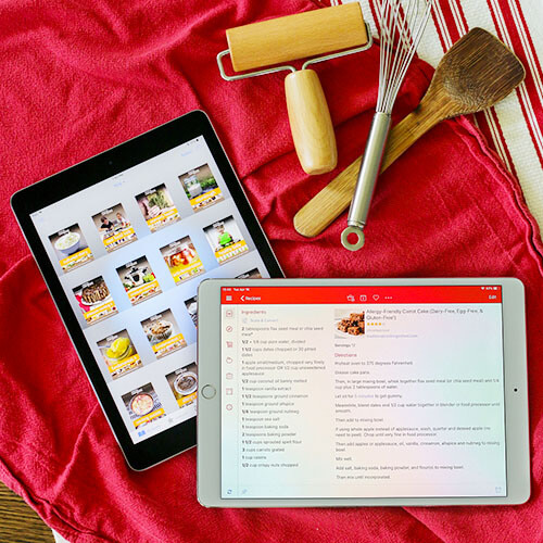 two iPads lying next to each other on a red tea towel with a recipe app and eBooks pulled up on the screens, next to kitchen tools such as a whisk and wooden spoon
