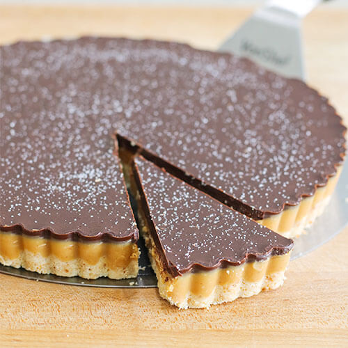 chocolate peanut butter tart with a wedge cut out and slightly separated from the rest of it