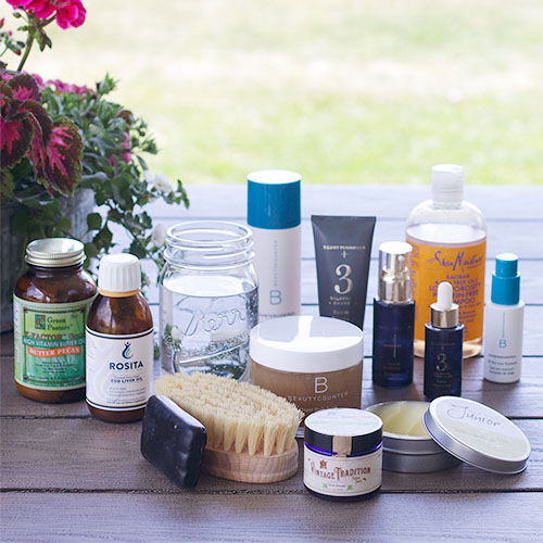 array of many different non-toxic products on a picnic table, including cod liver oil, tallow balm, Shea Moisture shampoo, BeautyCounter products, a dry brush, etc.