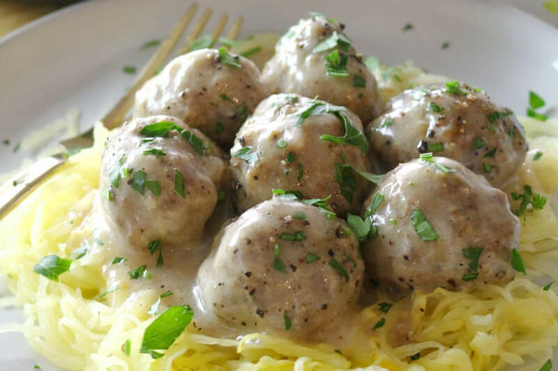 seven oven-baked Swedish meatballs on a bed of spaghetti squash sprinkled with fresh herbs