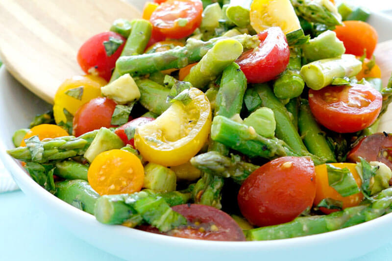 photo of asparagus tomato salad in a blue bowl with a wooden serving spoon
