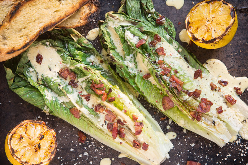 grilled Romaine caesar salad with grilled bread, grilled citrus, and whole heads of grilled romaine lettuce topped with dressing and bacon