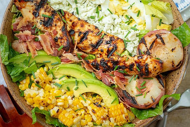 grilled chicken salad, with corn, sliced avocado, green onion, bacon, and potato
