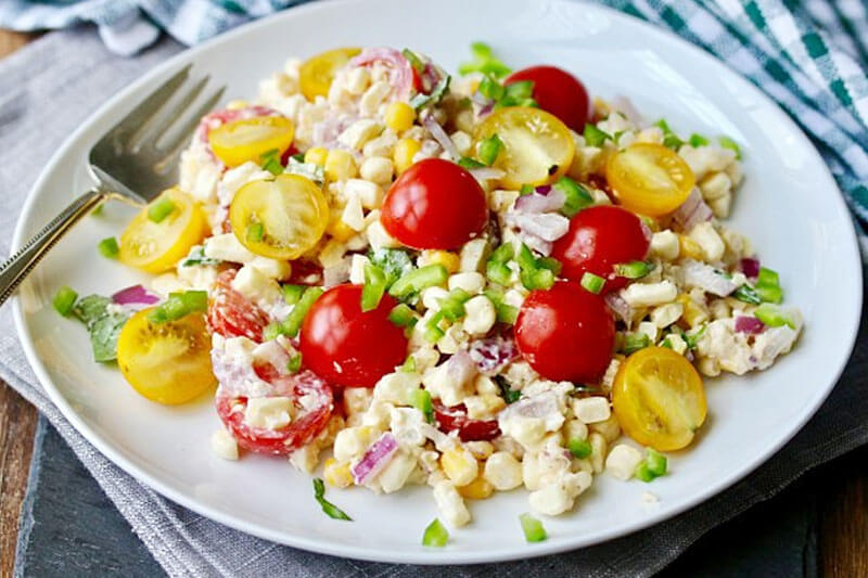 white ceramic plate of Mexican street corn salad, with grape tomatoes on top, next to a fork