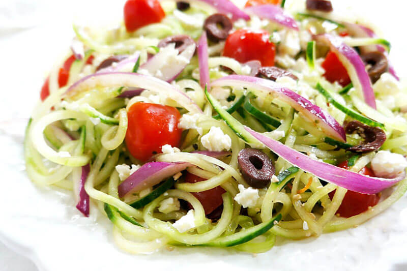 spiralized Greek cucumber salad with onions, olives, feta, tomatoes, and cucumber