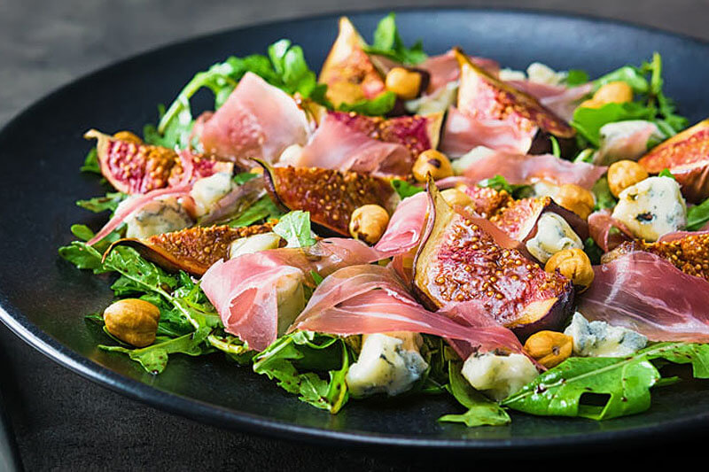 a dark-colored plate of roasted fig salad with thinly sliced meat and chickpeas on a bed of greens