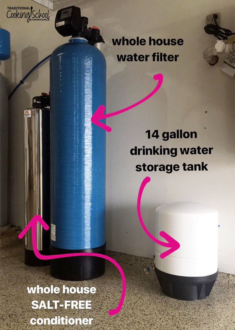 image of a whole house water filtration system set-up in a garage, with text overlay and arrows pointing to each water tank: the whole house water filter, the whole house salt-free conditioner, and the 14 gallon drinking water storage tank