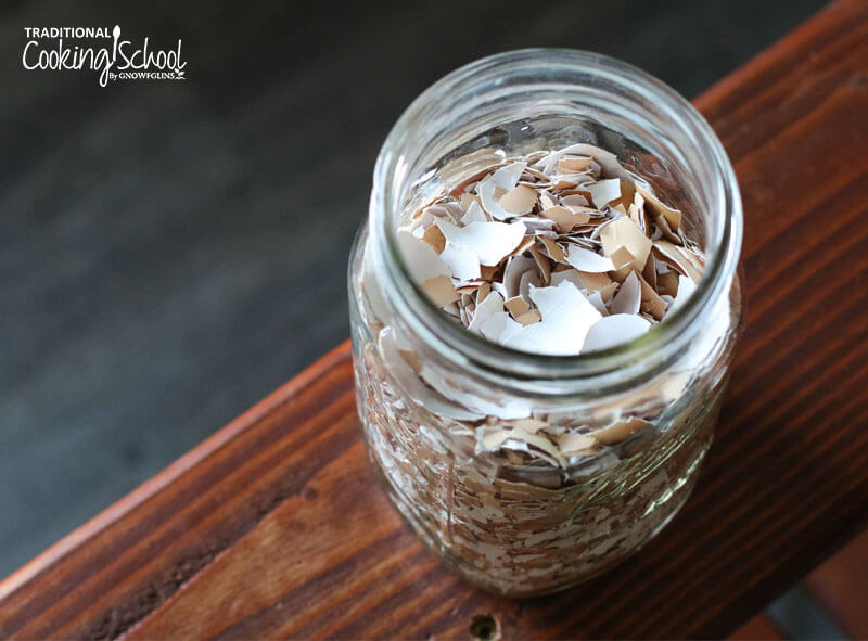 quart sized Mason jar almost full of crushed dried egg shells, sitting on a wooden surface
