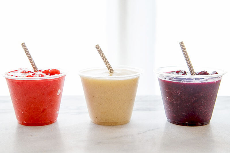 a row of three fruity coconut water slushies with straws sticking out, one bright red, one a natural light peachy brown, and the last one a dark purple burgundy color reminiscient of blackberries