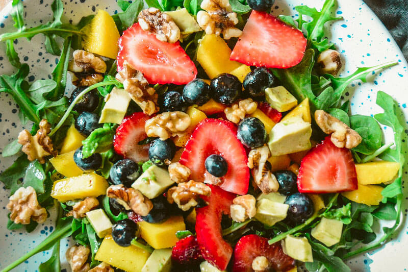 colorful summer salad featuring fruit like strawberries and blueberries as well as walnuts and avocado chunks on a bed of arugula