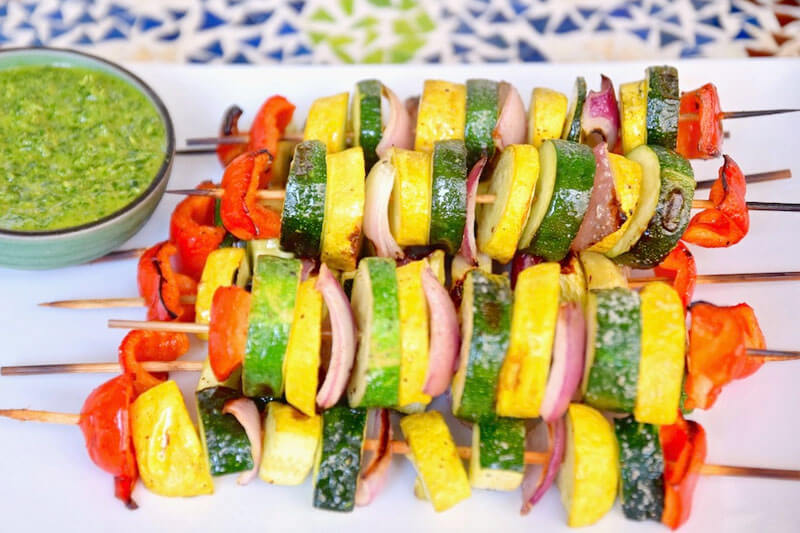 an array of colorful grilled veggie shish kabobs, including zucchini and squash, onion, and pepper slices, next to a bowl of green dipping sauce