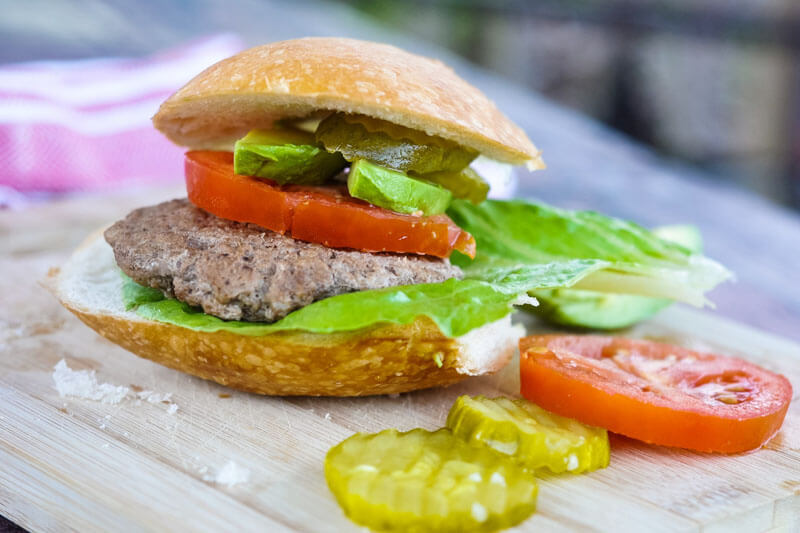 a healthy, classic burger on a wooden cutting board, with tomato, avocado, lettuce, and pickle slices for toppings