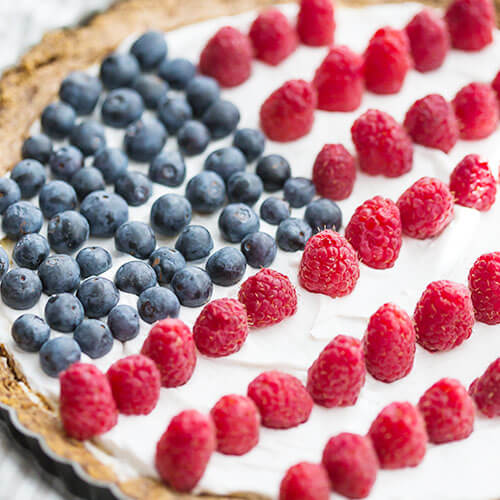 a red white and blue dessert, some kind of cheesecake or tart with blueberries and raspberries decorating the top in the shape of a flag