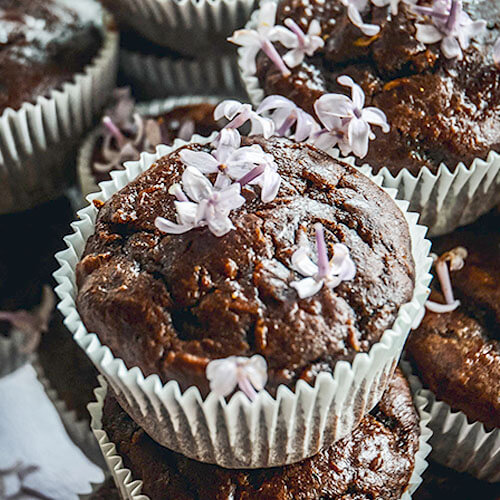 an asymmetrical stack of gooey and moist-looking chocolate muffins in pale blue muffin cups, sprinkled with light purple flowers on top