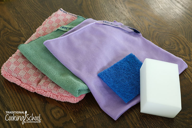 array of Norwex cleaning cloths, including a purple polishing cloth, next to a blue scrubbie and white magic eraser
