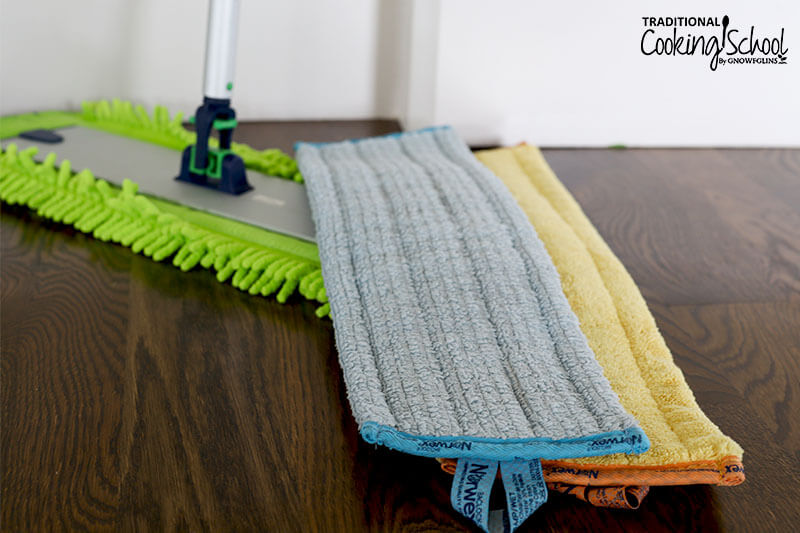 Norwex mop resting on a hard wood floor, featuring the dry, wet, and chenille mop cloths