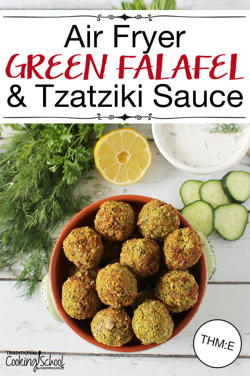 "red ceramic bowl of falafel on a white wooden background with fresh dill, half a lemon, cucumber slices, and a bowl of tzatziki sauce with text overlay: ""Air Fryer Green Falafel & Tzatziki Sauce (THM:E)"""