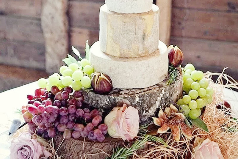 beautiful cheese wheel on a platter made out of the cross-section of a tree, decorated with flowers, figs, and grapes, as a representation of a wedding cake alternative