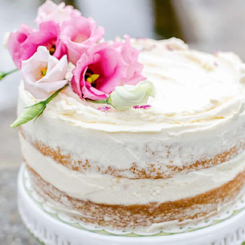 beautiful naked cake on a white ceramic cake stand, with white frosting between the layers and pink flowers on top