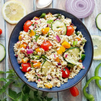 overhead shot of a dark blue ceramic bowl of cold brown rice salad with garden veggies like cherry tomatoes, sliced cucumber, bell pepper, and diced onion, on a wooden backdrop surrounded by prettily sliced veggies