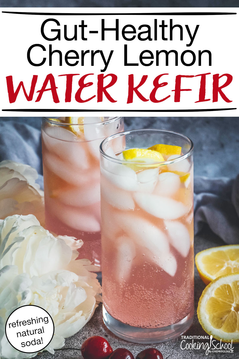 """two clear drinking glasses full of a ice cubes and a fizzy light pink liquid, topped with lemon slices, and surrounded by white flowers, cherries, and lemon halves, with text overlay: """"Gut-Healthy Cherry Lemon Water Kefir (refreshing natural soda!)"""""""