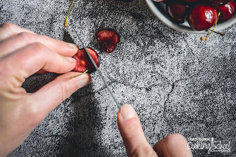 woman's hands holding a knife and cutting a cherry into small pieces