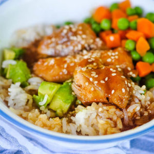 blue and white ceramic bowl of chicken pieces covered in a honey colored glaze with sesame seeds sprinkled over top, next to avocado chunks, small carrot cubes, and peas, on a bed of rice