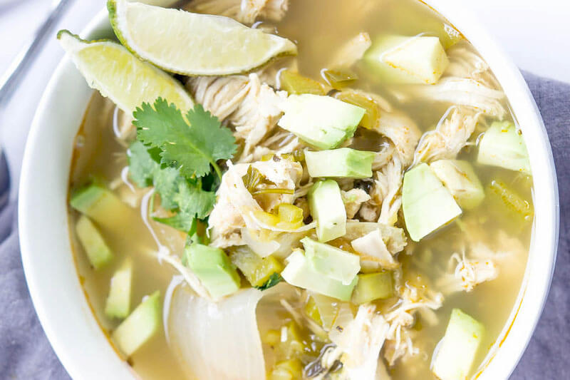 overhead shot of green chile chicken soup, garnished with sliced limes, avocado chunks, and fresh herbs