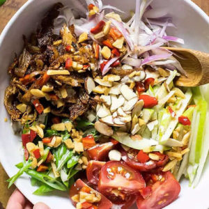 overhead shot of a bowl of crispy Thai chicken salad, with slivered almonds, a variety of veggies, and leftover chicken meat